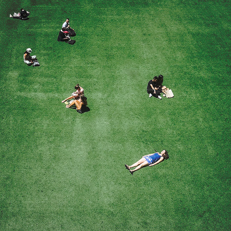 high-angle-image-of-people-sitting-on-fake-grass