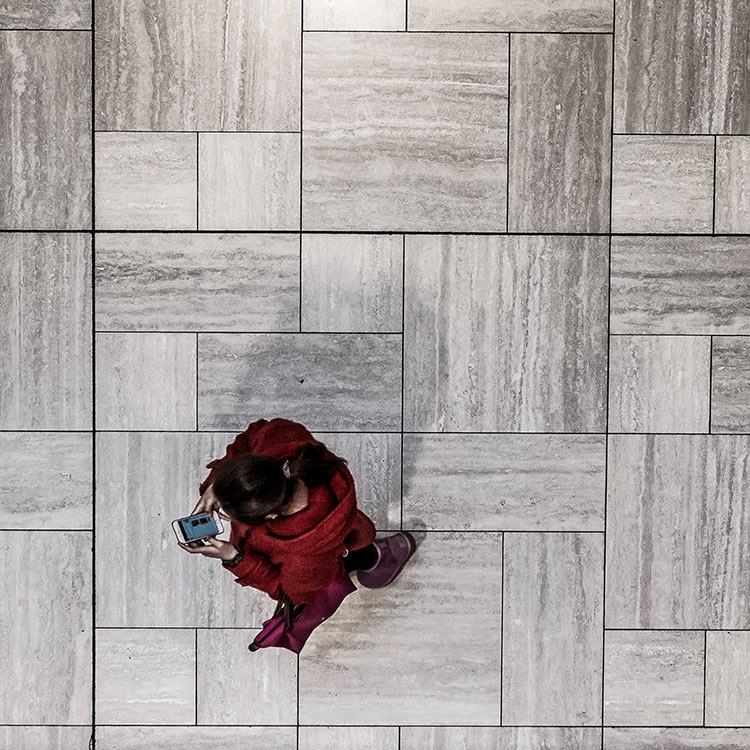 overhead-shot-of-a-woman-wearing-red-and-looking-at-mobile-phone