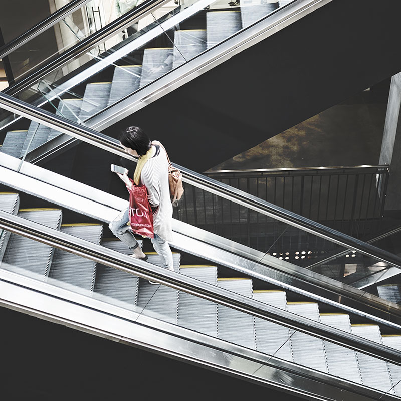 Woman-checking-phone-on-escalator