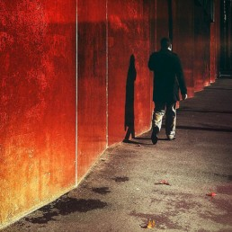 Man-walking-next-to-a-red-wall-